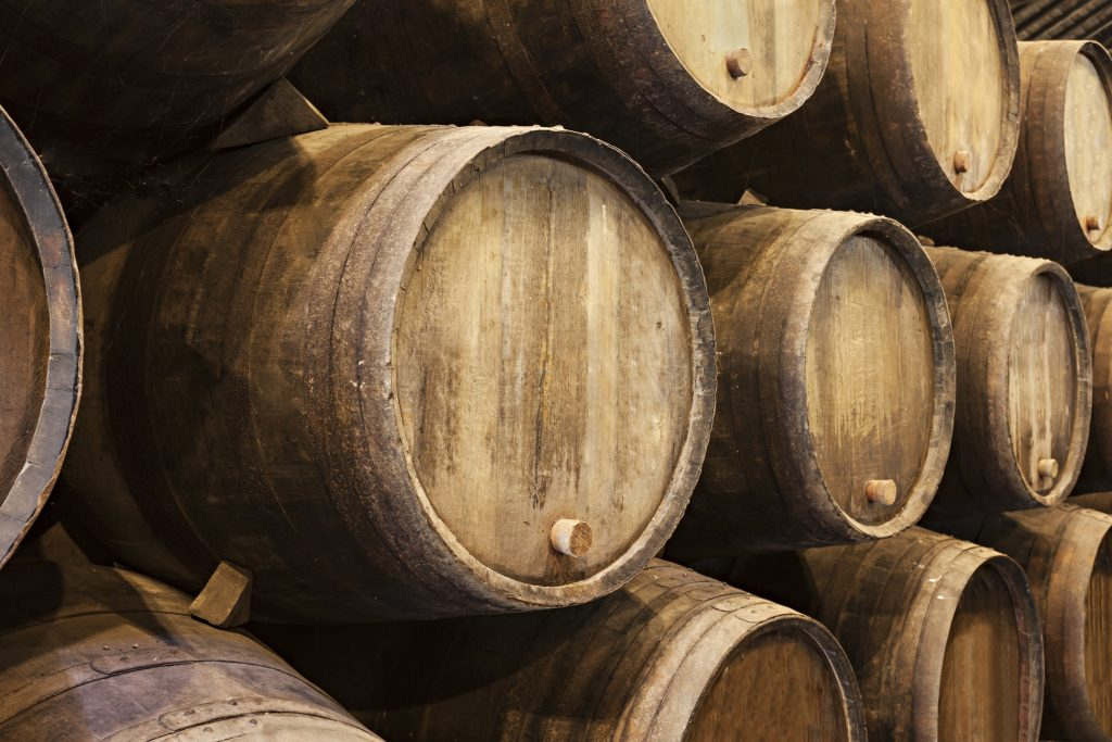 Stacked wooden wine barrels in Porto
